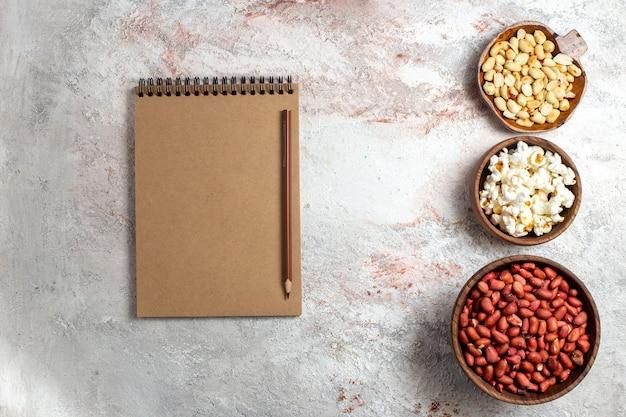 Vue de dessus différentes noix avec du maïs soufflé sur un espace blanc