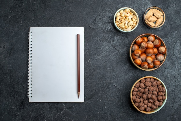 Vue de dessus différentes noix noisettes et arachides sur fond gris noix snack usine alimentaire de noix