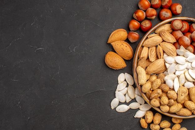 Vue de dessus de différentes noix noix fraîches à l'intérieur du plateau sur une surface sombre