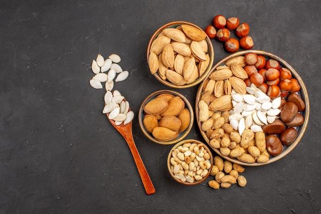 Vue de dessus de différentes noix noix fraîches à l'intérieur de pots sur une surface sombre