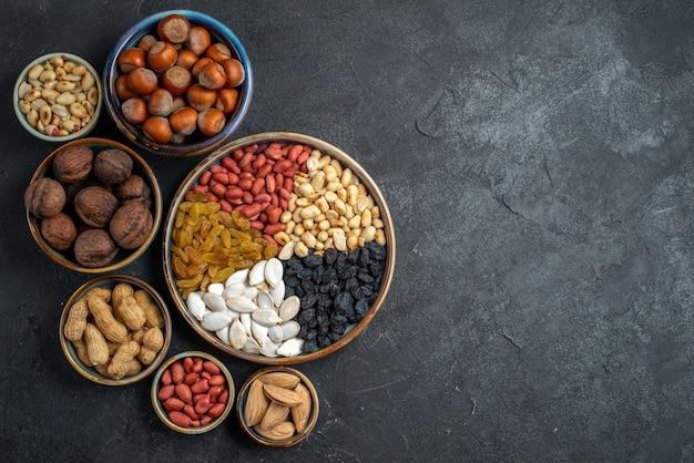 Vue de dessus différentes noix avec des raisins secs et des fruits secs sur le fond gris noix snack raisin sec fruits secs noix