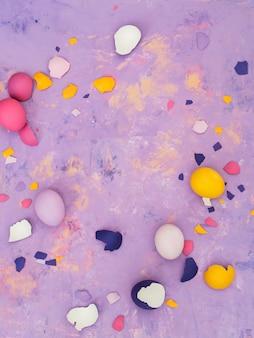 Vue de dessus de différentes oeufs colorés et coquille d'oeuf dispersée sur fond abstrait.