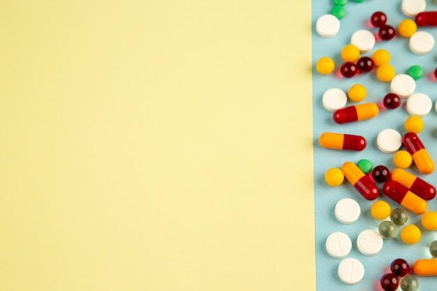 Vue de dessus différentes pilules sur fond coloré