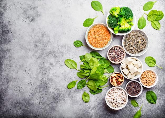 Vue de dessus de différentes sources de protéines végétaliennes avec un espace pour le texte : haricots, lentilles, quinoa, tofu, légumes, noix, pois chiches, riz, fond de pierre. une alimentation végétarienne saine et équilibrée pour les végétaliens