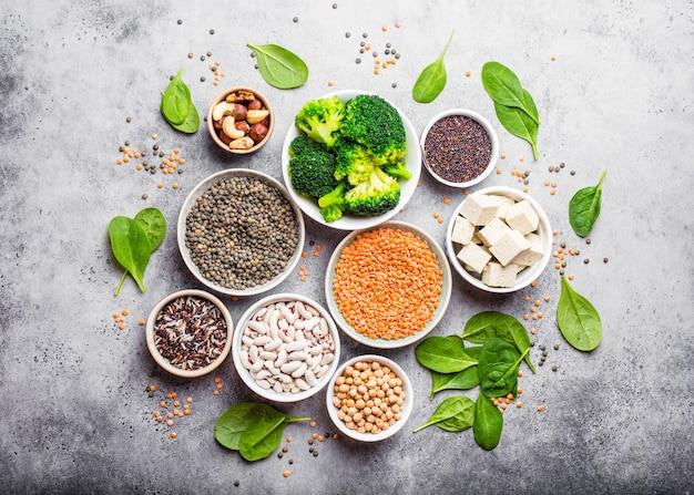 Vue de dessus de différentes sources de protéines végétaliennes : haricots, lentilles, quinoa, tofu, légumes, épinards, noix, pois chiches, riz, fond rustique en pierre. une alimentation végétarienne saine et équilibrée pour les végétaliens