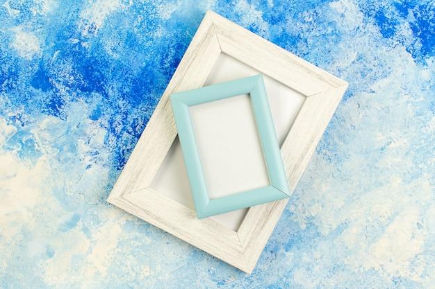 Vue de dessus de différentes tailles de cadres photo vierges sur le lieu de copie bleu blanc grunge
