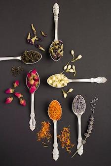 Vue de dessus de différentes variétés de thé dans les cuillères en argent sur la surface noire