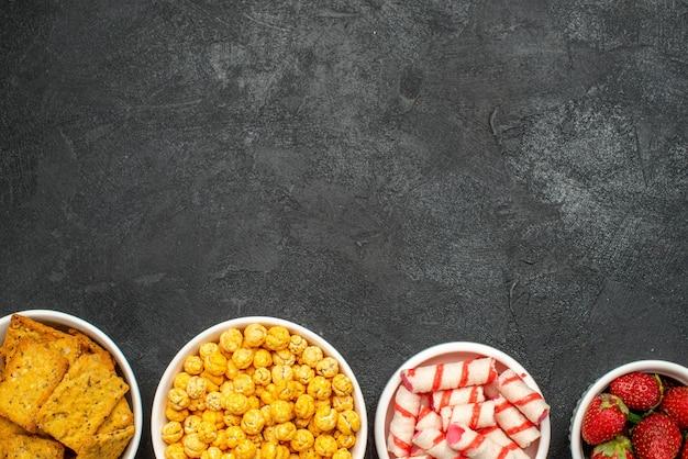 Vue de dessus différents aliments chips fruits et bonbons
