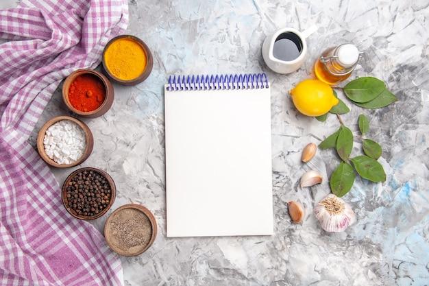 Vue de dessus différents assaisonnements à l'ail sur des fruits de poivre sel de table blanc