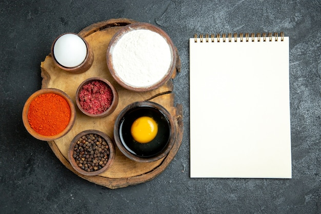 Vue de dessus différents assaisonnements avec bloc-notes de farine et oeuf sur l'espace gris