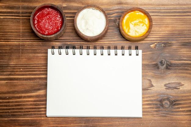 Vue de dessus de différents assaisonnements avec bloc-notes sur une table en bois marron cahier de couleur poivre épicé
