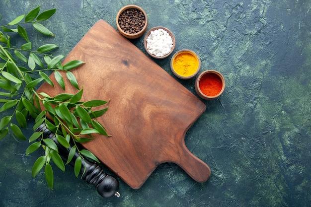 Vue de dessus différents assaisonnements avec bureau en bois marron sur la surface bleu foncé couleur bois coutellerie forte arbre cuisine verte