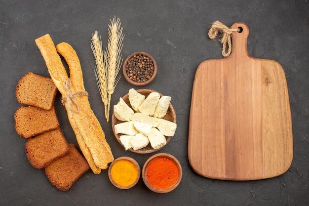 Vue de dessus de différents assaisonnements avec du fromage et des miches de pain noir sur fond noir