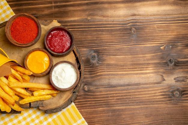 Vue de dessus de différents assaisonnements avec des frites sur un repas de restauration rapide de pommes de terre de table en bois marron