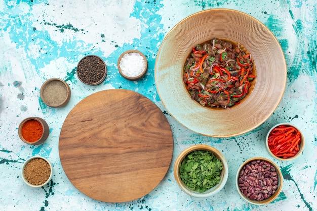 Vue de dessus de différents assaisonnements avec des haricots verts sur bleu clair, ingrédient poivron repas légume