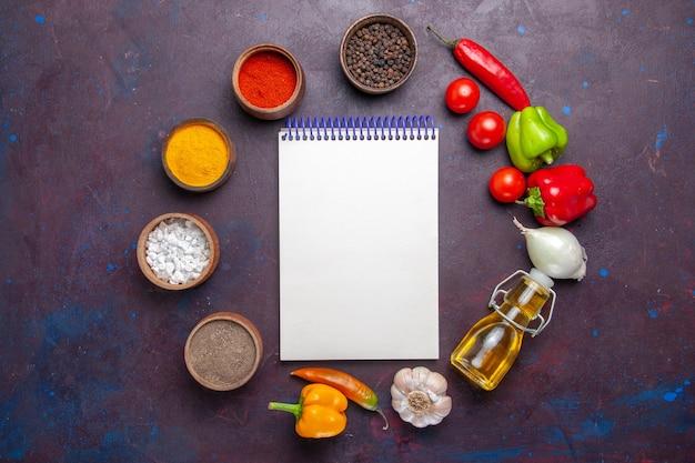 Vue de dessus différents assaisonnements avec de l'huile et des légumes sur la surface sombre des légumes alimentaires repas épicé