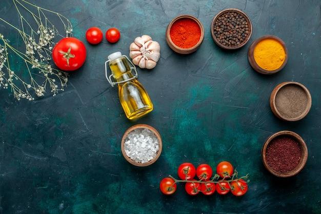 Vue de dessus différents assaisonnements avec de l'huile et des tomates sur fond vert foncé ingrédient produit repas alimentaire légume