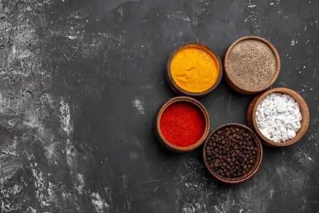 Vue de dessus différents assaisonnements à l'intérieur de petits pots sur la table sombre poivre couleur épice