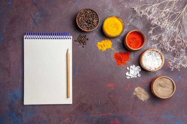 Vue de dessus différents assaisonnements à l'intérieur de pots sur le fond sombre soupe sauce repas épicé au poivre