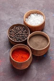 Vue de dessus différents assaisonnements à l'intérieur de pots sur une surface sombre ingrédient produit alimentaire photo