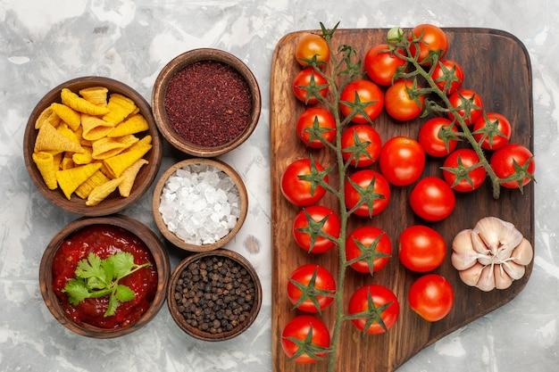 Vue de dessus différents assaisonnements à l'intérieur de pots avec des tomates cerises sur une surface blanche