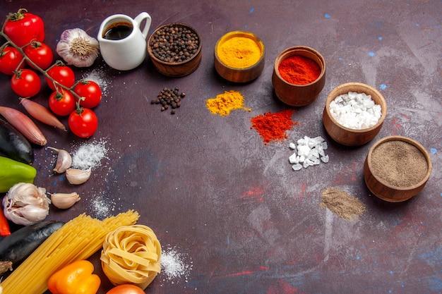 Vue de dessus différents assaisonnements avec des légumes sur fond sombre soupe sauce repas épicé au poivre