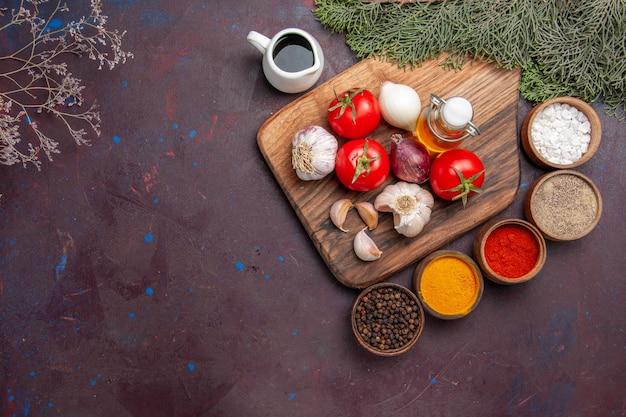 Vue de dessus de différents assaisonnements avec des légumes frais sur un sol noir arbre de plante de couleur de repas mûr
