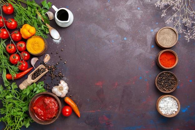 Vue de dessus différents assaisonnements avec des légumes verts et des légumes sur l'espace sombre