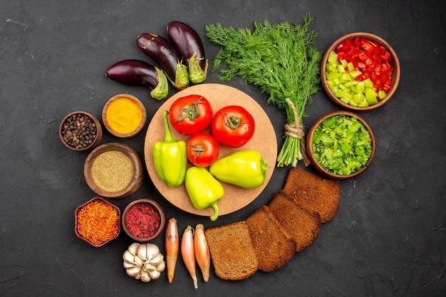 Vue de dessus différents assaisonnements avec des légumes verts et des miches de pain noir sur fond sombre assaisonnements pour salades pain diététique