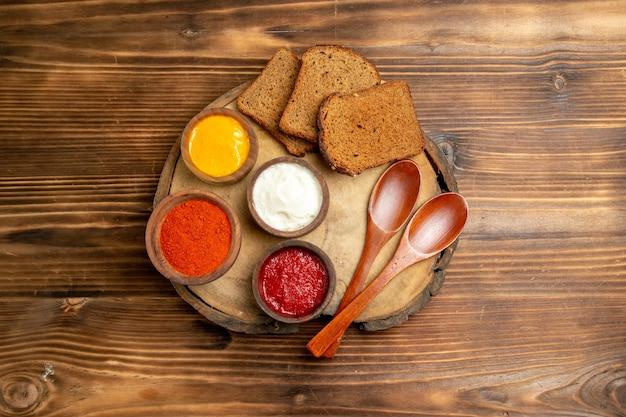 Vue de dessus de différents assaisonnements avec des miches de pain noir sur une table en bois marron