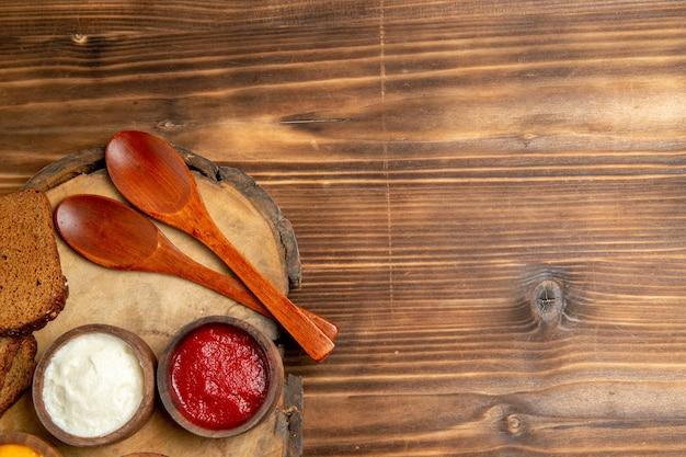 Vue de dessus de différents assaisonnements avec des miches de pain noir sur une table brune