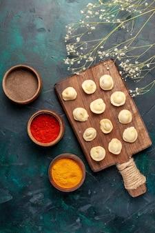 Vue de dessus différents assaisonnements avec de la pâte crue sur l'ingrédient alimentaire cru de la pâte de surface bleue