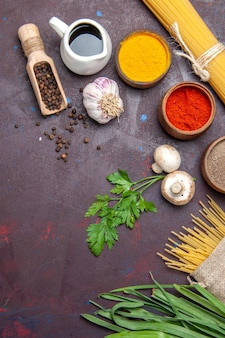 Vue de dessus différents assaisonnements avec des pâtes crues et des champignons sur une surface sombre repas de produits alimentaires crus