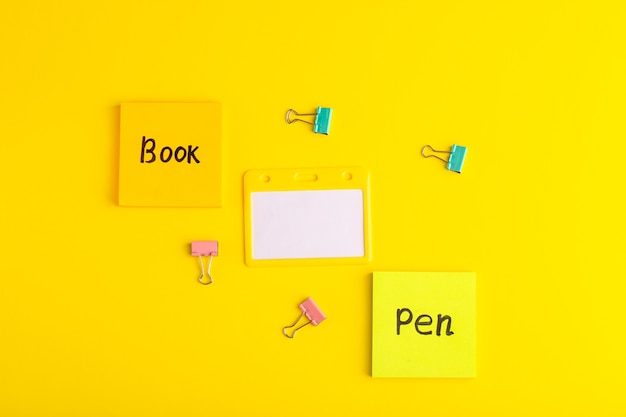 Vue de dessus différents autocollants avec des écritures sur le bureau jaune