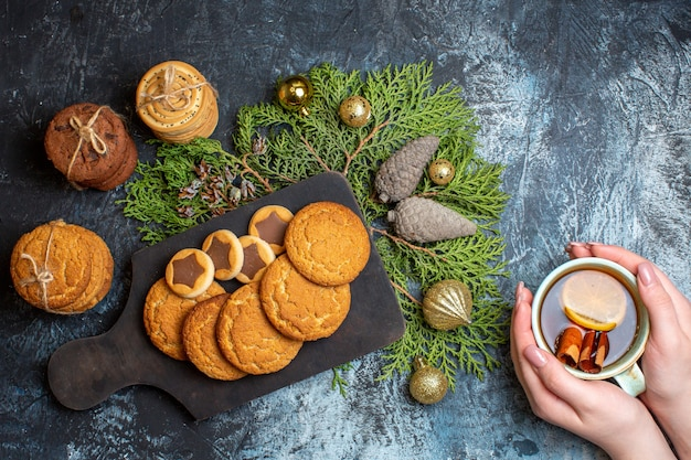 Vue de dessus différents biscuits délicieux avec une tasse de thé sur une table lumineuse