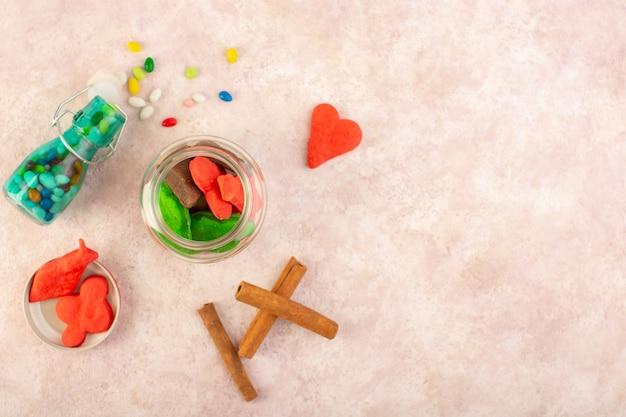 Vue de dessus de différents biscuits sucrés et délicieux avec de la cannelle et des bonbons sur la surface rose