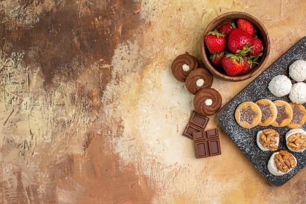 Vue de dessus différents bonbons avec des biscuits et des fruits sur le bureau léger