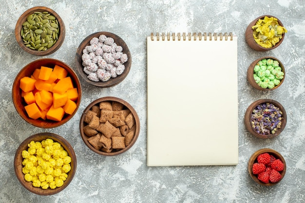 Vue de dessus différents bonbons avec des graines et de la citrouille sur un thé de bonbons de couleur de fleur de surface blanche
