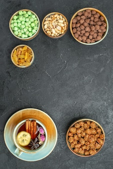 Vue De Dessus De Différents Bonbons Sucrés Aux Noix Et Tasse De Thé Sur Gris Noir Photo gratuit