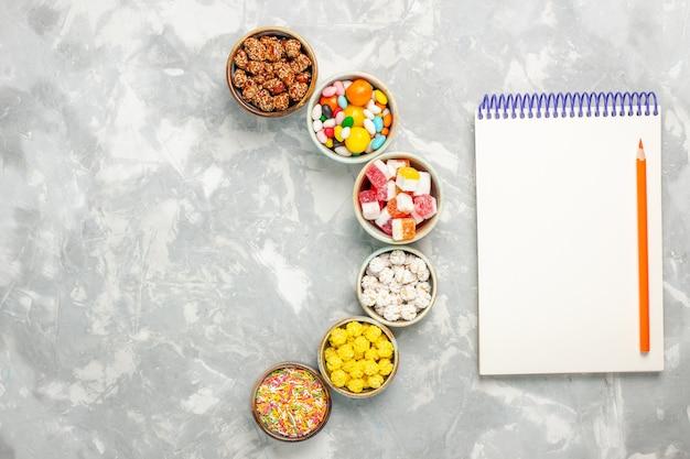 Vue de dessus de différents bonbons sucrés avec des guimauves et bloc-notes sur une surface blanche