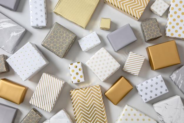 Vue de dessus différents coffrets cadeaux emballés sur marbre blanc multicolore divers cadeaux donnant le paquet