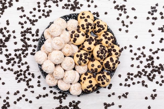 Vue de dessus différents cookies avec des morceaux de chocolat sur une surface blanche