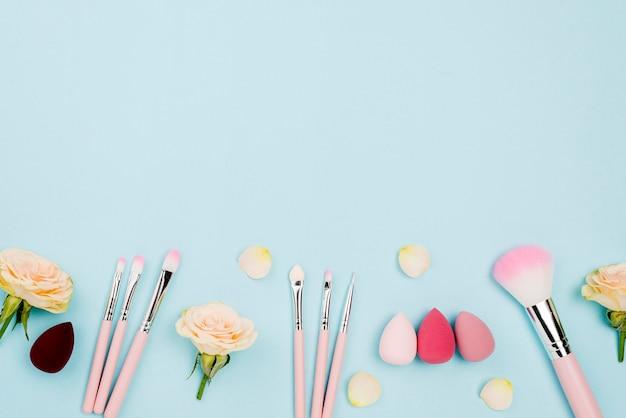Vue de dessus différents cosmétiques avec espace copie sur fond bleu