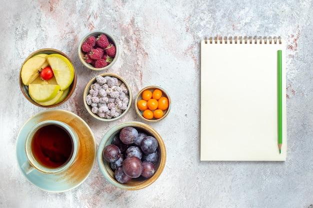 Vue de dessus différents fruits composition fruits frais avec petit gâteau et thé sur fond blanc fruits moelleux vitamine santé mûrs