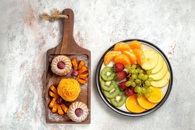Vue de dessus différents fruits composition fruits frais et tranchés sur fond blanc fruits mûrs couleur douce santé