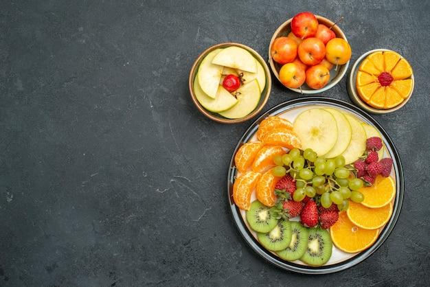 Vue de dessus différents fruits composition fruits frais et tranchés sur fond sombre fruits frais moelleux santé mûrs