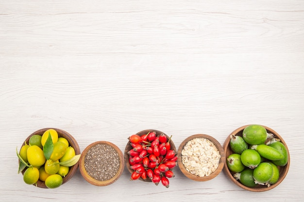 Vue de dessus différents fruits frais à l'intérieur des assiettes sur fond blanc régime mûr exotique vie saine couleur tropicale