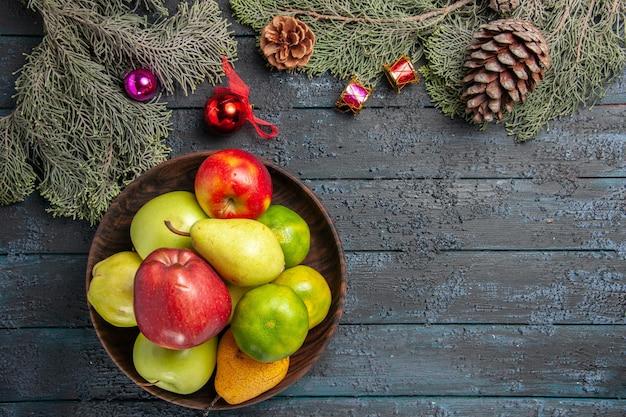 Vue de dessus différents fruits frais à l'intérieur de la plaque sur la composition de couleur de fruits de bureau bleu foncé frais mûrs