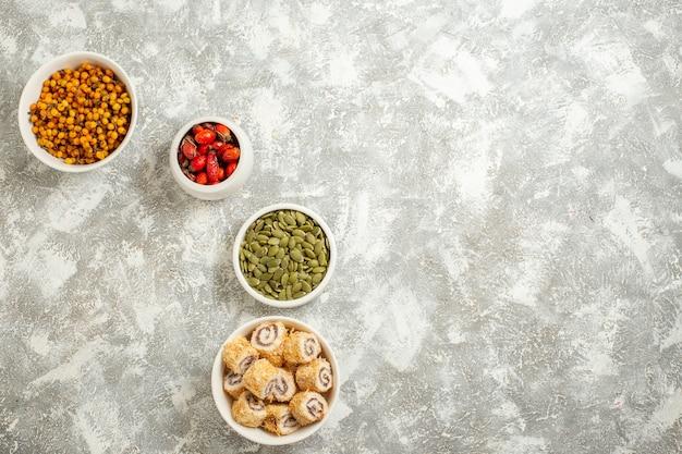 Vue de dessus différents fruits avec des graines et des petits pains sucrés sur fond blanc