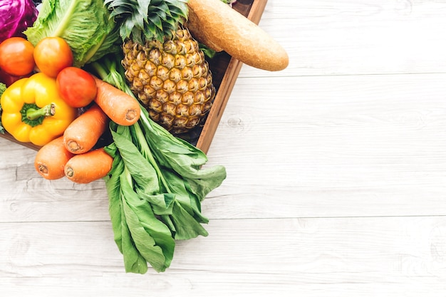 Vue de dessus de différents fruits et légumes frais sur la table en bois blanc